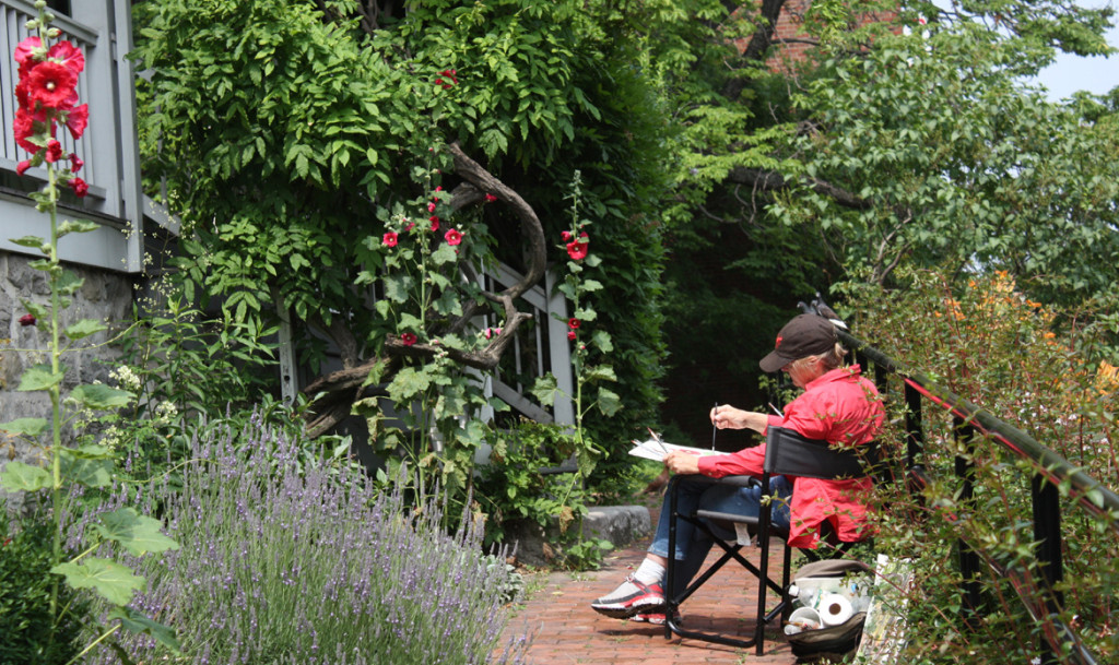 View of artist painting on the grounds of the Dyckman Farmhouse Museum