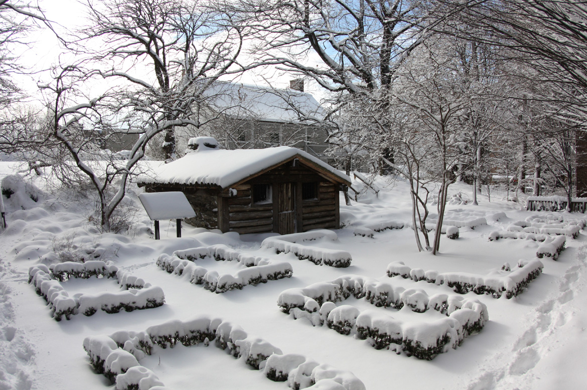 A winter view of the Military Hut, Formal Garden and rear facade of the Dyckman Farmhouse.