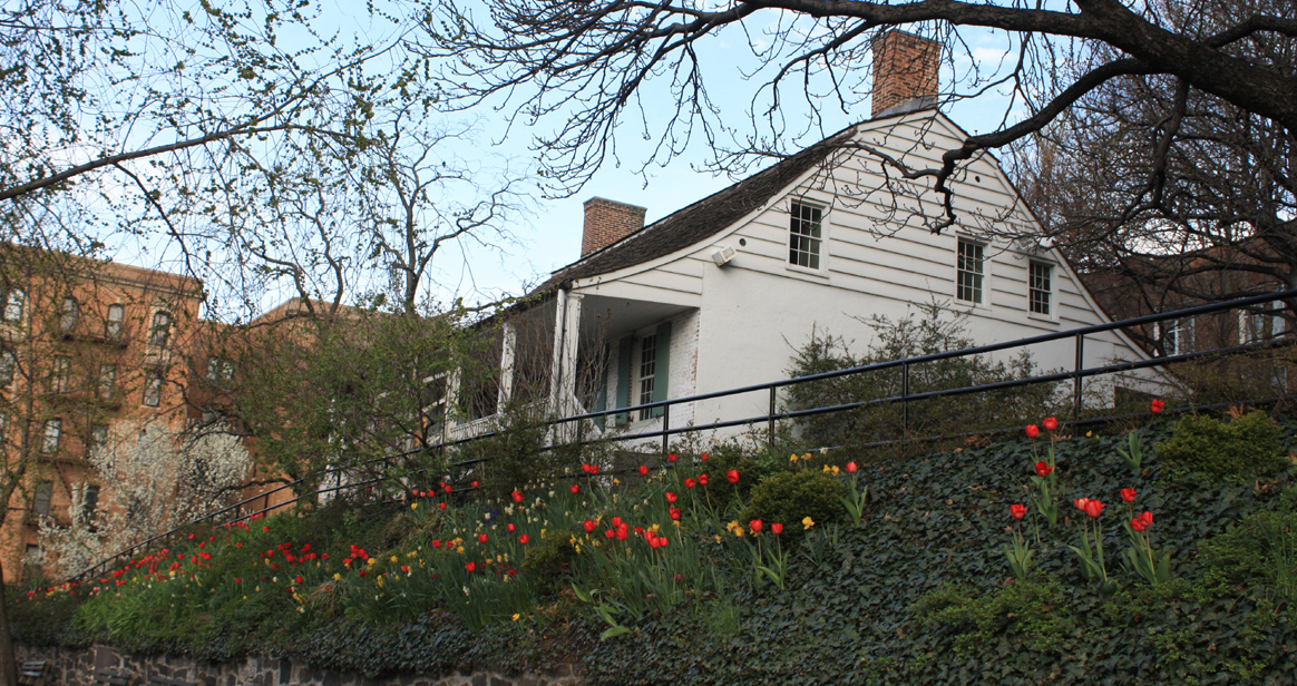 View of the front of Dyckman Farmhouse in the spring.